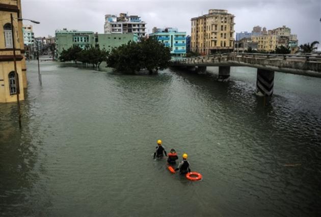 Des sauveteurs cubains avancent dans une rue inondée de La Havane après le passage de l'ouragan Irma le 10 septembre 2017- YAMIL LAGE
